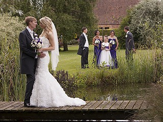 Bride and groom on the bridge over a garden pond.